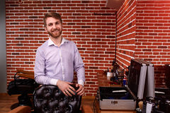 Barber expert smiling and looking at camera and keeping hand on chair while standing at barbershop against brick wall. Portrait of hairdresser in the shirt stock photos