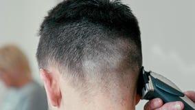 Barber Female Cuts Hair vid clipperen på baksida av huvudet av den brunhåriga mannen i salong lager videofilmer