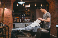 Barber finishing grooming and taking care of client's face Royalty Free Stock Photography