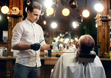 Barber finishing haircutting and shaving. Final stage of customer service in professional hairdressing salon for men. Barber finishing haircutting. Master stock image