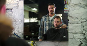 Barber Giving Client Haircut Reflected masculina en espejo almacen de video