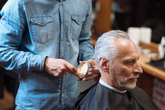 Barber going to style hair of client with gel Stock Image