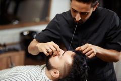 Barber grooming young man in chair Royalty Free Stock Photo