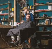 Barber with hair clipper in hand finished trimming. Hipster client getting haircut. Barber with hair clipper works on. Hairstyle for bearded men barbershop stock image