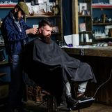 Barber with hair clipper works on haircut of bearded guy barbershop background. Hipster client getting haircut. Barber royalty free stock images