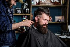 Barber with hair clipper works on haircut of bearded guy barbershop background. Hipster client getting haircut. Hipster. Hairstyle concept. Barber with clipper stock images