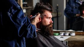 Barber with hair clipper works on hairstyle for bearded man barbershop background. Hipster lifestyle concept. Barber. Barber with hair clipper works on hairstyle stock photos
