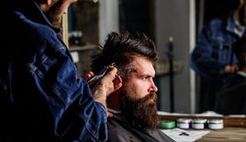 Barber with hair clipper works on hairstyle for bearded man barbershop background. Barber styling hair of brutal bearded. Barber with hair clipper works on royalty free stock image