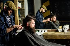 Barber with hair clipper works on hairstyle for man with beard, barbershop background. Barber styling hair of bearded. Barber with hair clipper works on stock photos