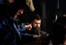 Barber with hair clipper works on hairstyle for man with beard, barbershop background. Barber styling hair of brutal. Barber with hair clipper works on hairstyle royalty free stock photos