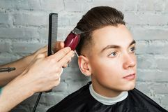 Barber hair styling of young guy in the barbershop on brick wall background, hairdresser makes hairstyle for a young man. Barber hair styling of young guy in royalty free stock image