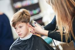 Barber or hair stylist at work. female hairdresser cutting child hair royalty free stock images