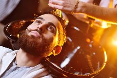 Barber or hairdresser washes the head of the client Royalty Free Stock Photography