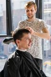Barber with hairdryer drying and styling hair of client. Styling concept royalty free stock photography