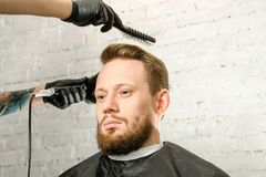 Barber hand in gloves cut hair and shaves adult gihger bearded man on a brick wall background. Close up portrait of a guy. Barber hand in gloves cut hair and stock photography