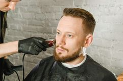 Barber hand in gloves cut hair and shaves adult gihger bearded man on a brick wall background. Close up portrait of a guy. Barber hand in gloves cut hair and royalty free stock images