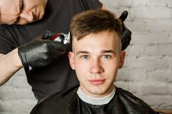 Barber hand in gloves cut hair and shaves young man on a brick wall background. Close up portrait of a guy. Barber hand in gloves cut hair and shaves young men stock photo