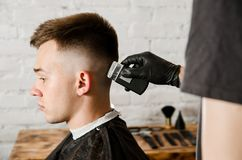 Barber hand in gloves cut hair and shaves young man on a brick wall background. Close up portrait of a guy. Barber hand in gloves cut hair and shaves young men stock images