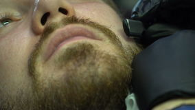 Barber hand shave beard with straight razor stock video