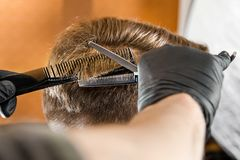 Barber hands cut hair and combing comb adult man on a brick wall background. Close up portrait of a guy. Barber hands cut hair and combing comb adult men on a stock photo