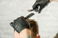 Barber hands cut hair and combing comb adult man on a brick wall background. Close up portrait of a guy. Barber hands cut hair and combing comb adult men on a stock photography