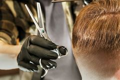 Barber hands cut hair and combing comb adult man on a brick wall background. Close up portrait of a guy. Barber hands cut hair and combing comb adult men on a royalty free stock photography