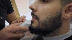 Barber leveled with a beard trimmer. Young cheovek in the cabin. stock footage