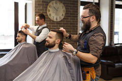 Barber make haircut with scissors to client at barbershop. Barber make haircut with scissors at barbershop. Stylish hairdresser in male hair salon stock photo