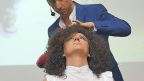 Barber makes a hair dryer dries hair curly brunette. In beauty salon stock video