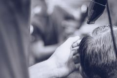 Barber combs hair client. royalty free stock photography