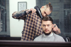 Barber makes a haircut Stock Images