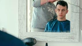 Barber Makes Haircut vid clipperen Man i frisersalongsalong Reflexion i spegel lager videofilmer