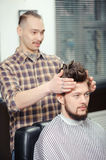 Barber makes hairstyling to a client Stock Images