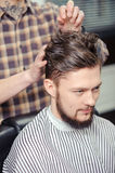 Barber makes hairstyling to a client Royalty Free Stock Photo