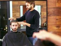 Barber makes men haircut at the beauty salon Stock Photos
