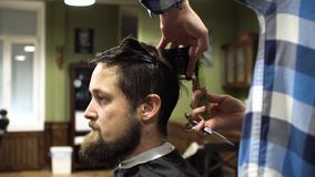 Barber making haircut of attractive bearded man in barbershop stock video