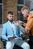 Barber making haircut of attractive bearded man in barber shop. So trendy and stylish. Brutal guy in modern Barber Shop. Barber making haircut of attractive royalty free stock image