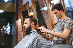Barber making haircut to handsome man with beard Stock Photo