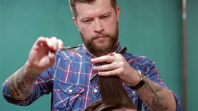Barber making haircut to hipster client stock video footage
