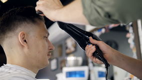 Barber making a hairstyle using a hair dryer. Slow motion. Professional barber is making man`s hairstyle using a hair dryer and a brush stock video footage