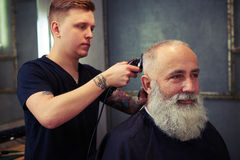 Barber making hear to handsome bearded man. Concentrated skillful barber making haircut to handsome attractive senior men with beard and working with electric Stock Image