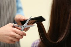 Barber making stylish haircut with professional scissors in beauty salon. Closeup stock photo