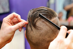 Barber modeling hair by comb at the hair salon Royalty Free Stock Photos