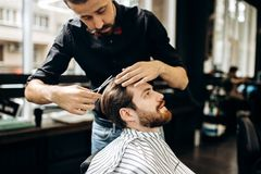 Barber with mustache dressed in a black shirt with a red bow tie makes a stylish hairstyle to young man in a barbershop royalty free stock photography