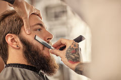 Barber with old-fashioned black razor Stock Photography