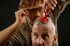 Barber paints with reddish paint of an elderly gray-haired citizen. In the studio stock image