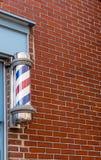 Barber Pole tradizionale dal muro di mattoni immagini stock