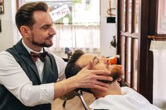 A barber attends to a customer in his barber shop stock photo
