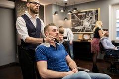 Barber preparing customer for shaving. Portrait of barber preparing customer for shaving Stock Photo