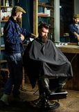 Barber preparing hair clipper for bearded man, barbershop background. Barber with clipper and brutal bearded client royalty free stock photo